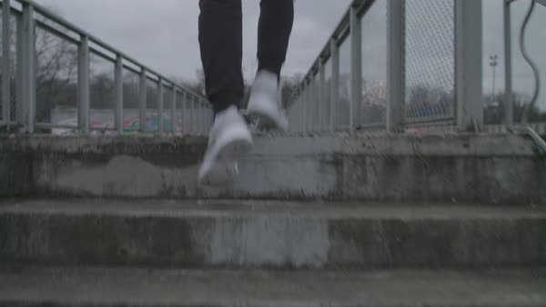 A young man running up stairs over a footbridge Royalty-free stock video