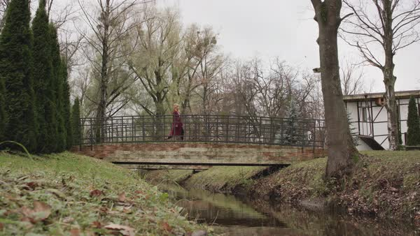 A young woman walking on a footbridge in a park Royalty-free stock video