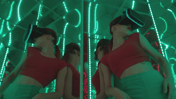 A young woman wearing VR goggles dancing sensuously in a mirrored room Royalty-free stock video