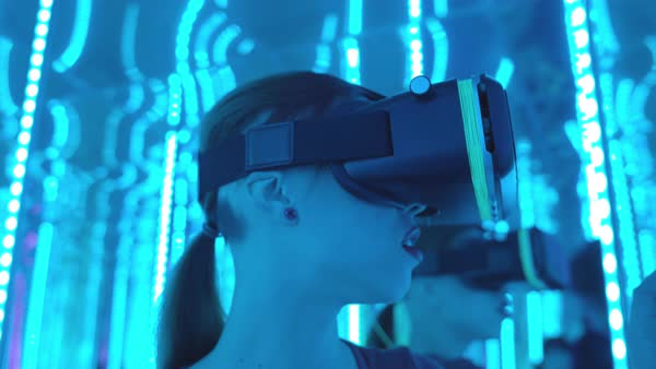 Close-up shot of a young woman wearing VR goggles standing in a mirrored room Royalty-free stock video