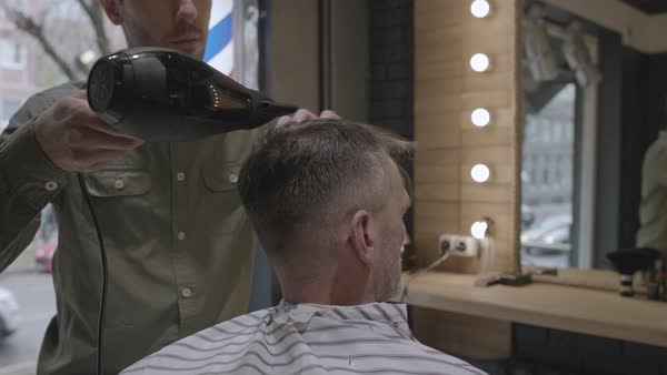 A hair stylist drying an older man's hair with a hair dryer Royalty-free stock video