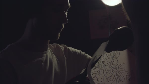 Close-up shot of a tattoo artist cutting a tattoo stencil Royalty-free stock video