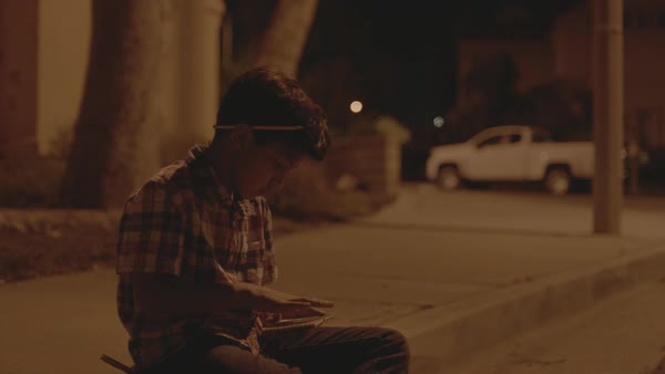Hand-held shot of a boy using a tablet outside at night Royalty-free stock video