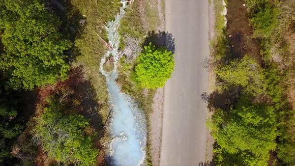 Aerial view looking down at road with hot spring and river flowing on both sides. Royalty-free stock video