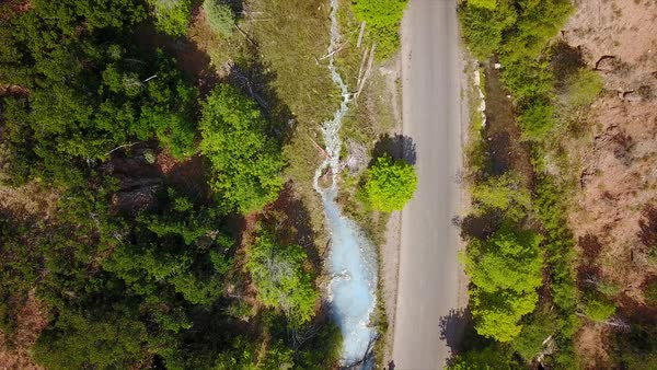 Aerial view moving towards hot spring flowing next to road. Royalty-free stock video