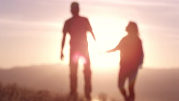 Out of focus couple walking in front of sun creating flares as they hold hands. Royalty-free stock video