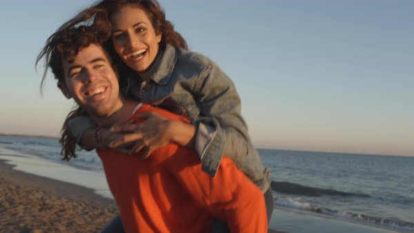 Young couple man carrying woman on back in sunset on beach Royalty-free stock video