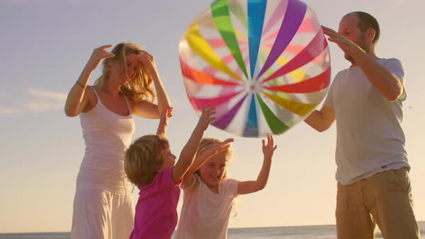 Young family playing with beach ball on beach Royalty-free stock video