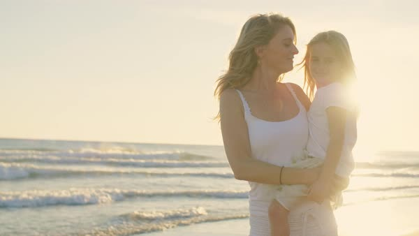 Mother and daughter standing on beach hugging and playing in sunset Royalty-free stock video