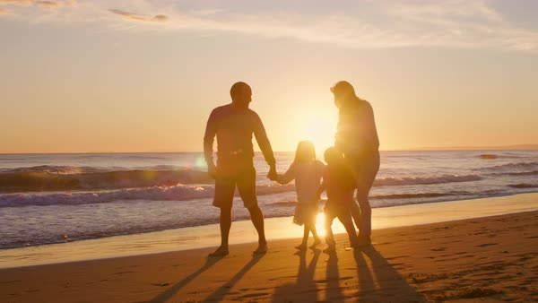 Young family walking and playing on beach with children holding hands in sunset Royalty-free stock video