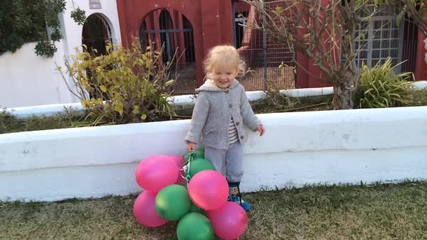 Zoom in shot of young girl standing by wall with balloons Royalty-free stock video