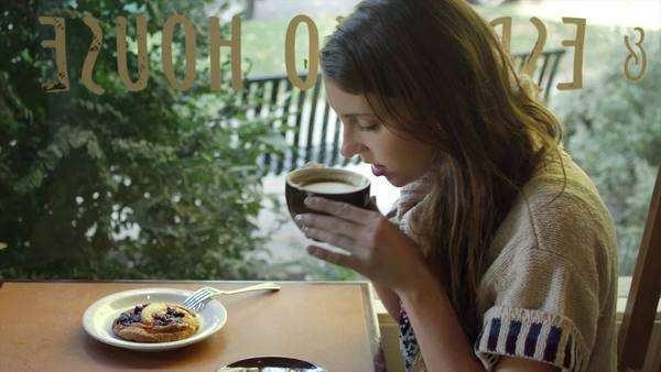A young woman sits at a table alone in a coffee shop and looks out the window while drinking coffee Royalty-free stock video