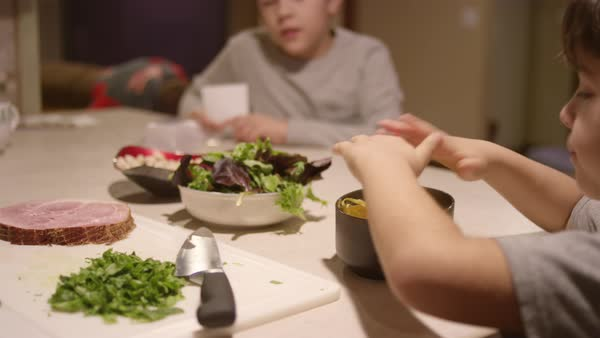 A little boy sets a bowl of cheese on the counter and sits with his brother Royalty-free stock video