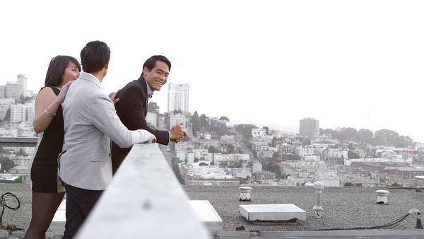 Two men are looking out over the city when a woman comes up behind them and says hello Royalty-free stock video