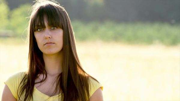 A young woman stands in a field with sunlight behind her with a serious face Royalty-free stock video
