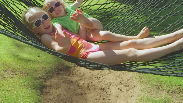 Two cute girls play around together on a swinging hammock smiling Royalty-free stock video
