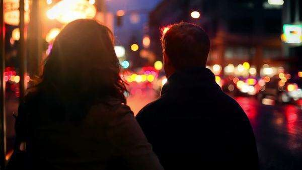 A couple walking away from the camera at night, with lots of city lights Royalty-free stock video