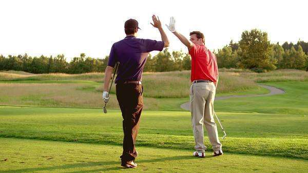 One golfer makes a good shot onto the green and gives a high five to his partner Royalty-free stock video