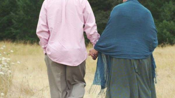 An older couple hold hands and walk through an open field during the day Royalty-free stock video