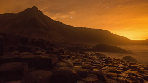 Timelapse of Giant's Causeway during sunset, mountain in background, Ireland Royalty-free stock video