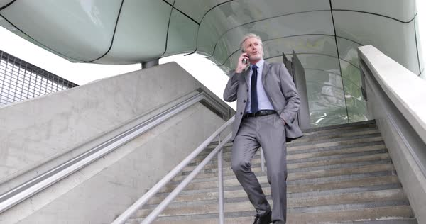 Senior businessman walking down stairs using smartphone outdoors Royalty-free stock video