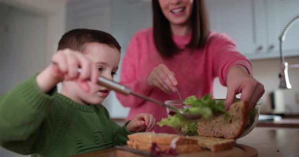 Boy making a sandwich with Mother helping Royalty-free stock video