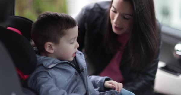 Mother putting son in car seat safely Royalty-free stock video