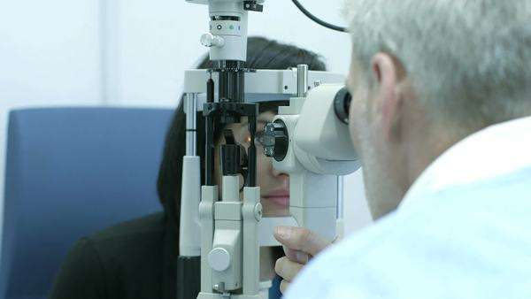 Female patient is examined by the Male Optician using the machine, close-up Royalty-free stock video