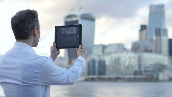 Business man takes a photo of the city scape and River Thames with his ipad/digital tablet Royalty-free stock video