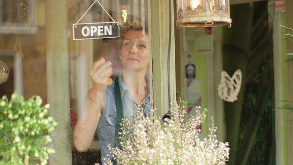 A Florist walks up to the window of her shop and flips the sign to open, medium long shot Royalty-free stock video