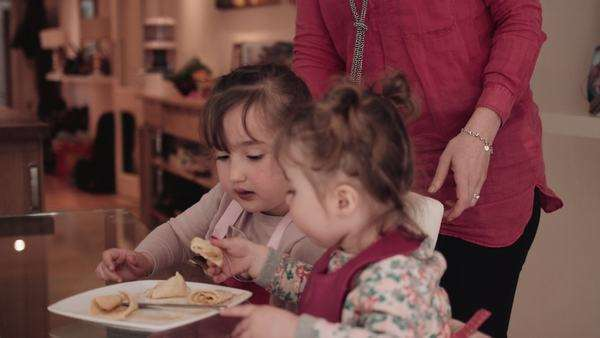 Girls eating pancake from plate at table, mother in background Royalty-free stock video