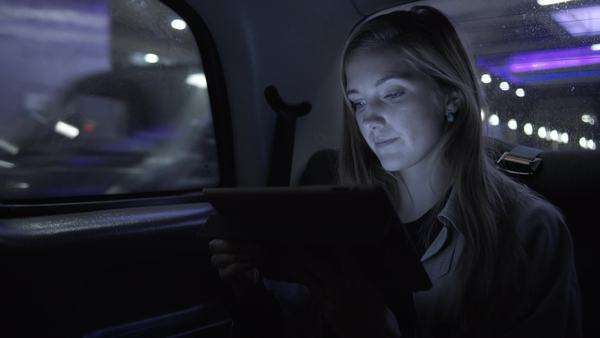 Young adult female in taxi using digital tablet at night Royalty-free stock video