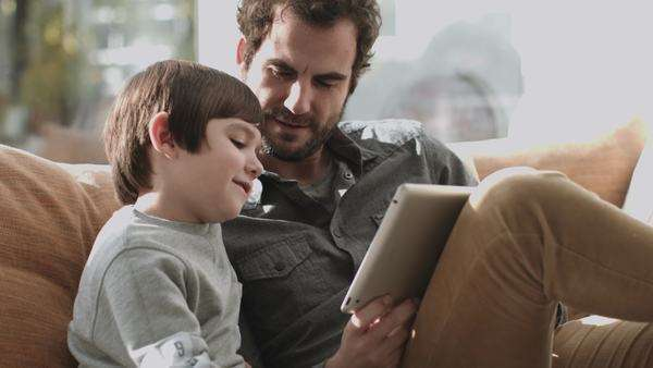 Father and son on the couch using digital tablet Royalty-free stock video