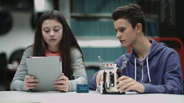 Teenage boy and girl working with digital tablet and robot in library Royalty-free stock video