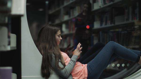 Teenage girl studying in library with smartphone, night time Royalty-free stock video