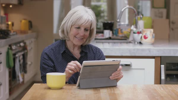 Senior woman reading on digital tablet on kitchen table Royalty-free stock video