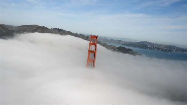 Aerial view over the Golden Gate Bridge, covered in fog. Royalty-free stock video