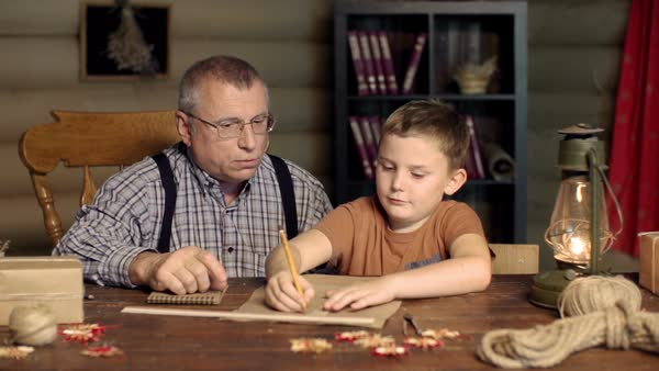 Grandfather teaching his elementary-age grandson to draft with a ruler Royalty-free stock video