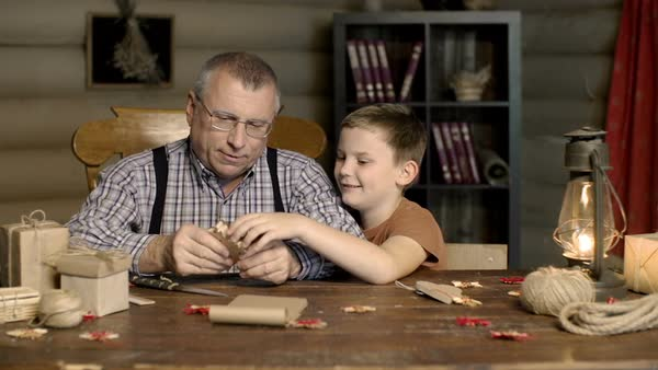 Loving grandfather making a wooden elk toy for his grateful grandson  Royalty-free stock video