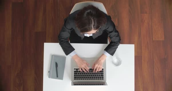 Directly above view of a businesswoman typing on laptop and closing it after finishing work  Royalty-free stock video
