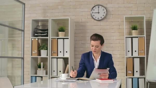 Close-up of young businesswoman looking at tablet and sipping her morning coffee in the office Royalty-free stock video