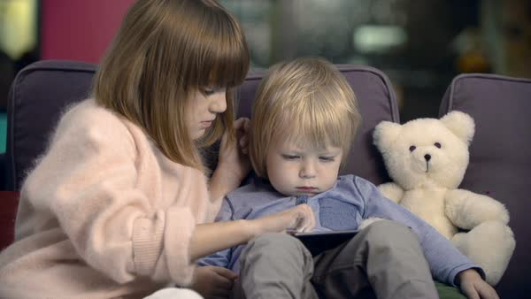 Lovely girl helping her little brother to use digital tablet Royalty-free stock video