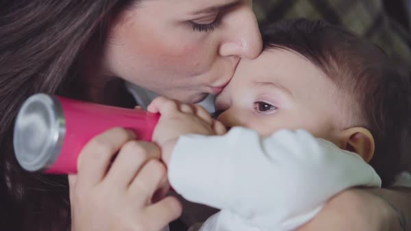 Young mother smooching forehead of her little son while he is drinking milk from baby bottle Royalty-free stock video