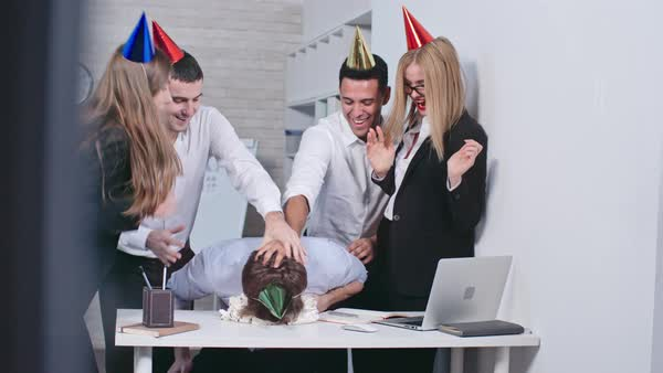 Office workers in party hats smashing face of their colleague into the birthday cake, clapping hands and laughing Royalty-free stock video
