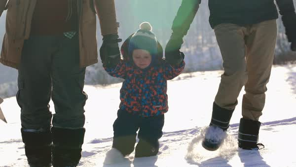 Loving parents walking with their cute baby son through snow at ski resort in Scandinavia and kissing him on both cheeks  Royalty-free stock video