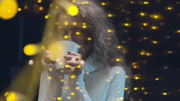 Young beautiful woman with long dark hair standing behind the window illuminated by yellow lights and drinking coffee Royalty-free stock video
