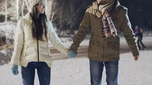 Tilt up of romantic young couple skating at outdoor rink holding hands in snowy winter evening  Royalty-free stock video