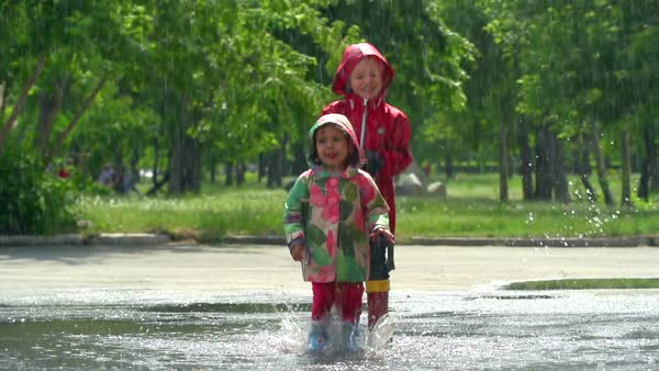 Two young kids jumping and splashing in a large puddle Royalty-free stock video