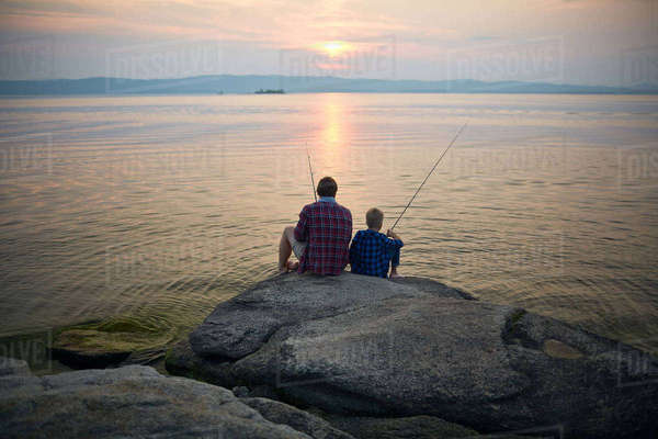 Two fishermen sitting on stone by lake in the evening Royalty-free stock photo