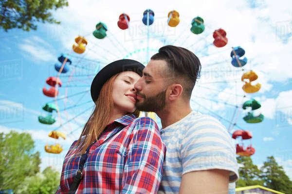 Amorous young couple kissing on background of amusement Royalty-free stock photo